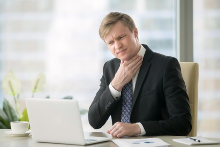 69803080 - young businessman working with laptop at desk in the office, hand at his neck, feeling unwell, have a sore throat, after loud screaming, loss of voice, irritation, pain, and itchiness, hard to swallow