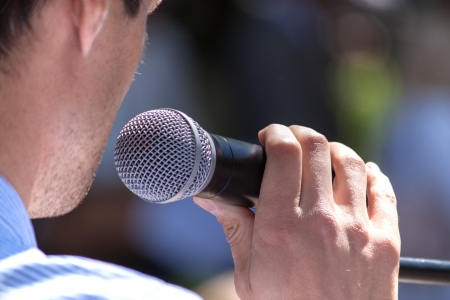 13884264 - speaker holds the microphone close up