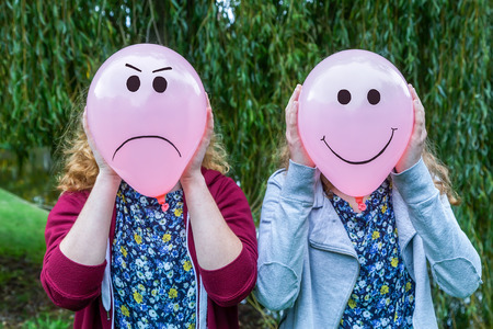 42354928 - two teenage girls holding balloons with smiling and angry facial expressions outdoors