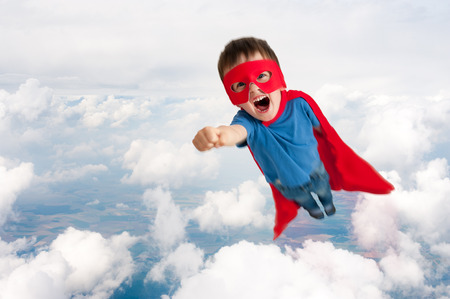 30116093 - superhero boy child flying upwards through the clouds