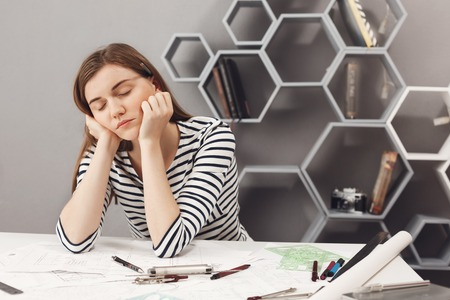88689849 - close up portrait of sleepy charming young european freelance engineer girl fall asleep on working place during preparations to meeting with team leader to talk about work mistakes